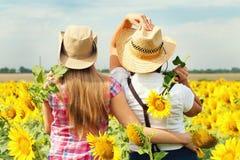 Schöne Mädchen in einem Cowboy Hats am Sonnenblumen-Feld Stockfotos