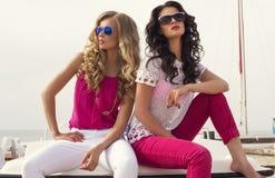 Schöne Mädchen mit der Sonnenbrille, die auf Sommer aufwirft, setzen auf den Strand Stockbild