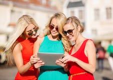 Schöne Mädchen toursits, die Tabletten-PC untersuchen Stockfotografie