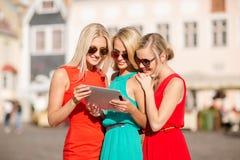 Schöne Mädchen toursits, die Tabletten-PC untersuchen Lizenzfreie Stockbilder
