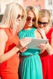 Schöne Mädchen toursits, die Tabletten-PC untersuchen Lizenzfreies Stockfoto