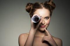 Schöne Mädchenblicke in einem Teleskop in der Papierrolle kundschaften lizenzfreies stockfoto
