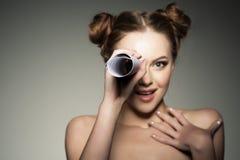 Schöne Mädchenblicke in einem Teleskop in der Papierrolle kundschaften lizenzfreie stockbilder