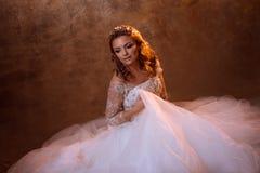 Schöne Mädchenbraut im luxuriösen Hochzeitskleid, das auf dem Boden, Porträt in den goldenen Tönen, Effekte des grellen Glanzes s Lizenzfreies Stockbild