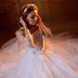 Schöne Mädchenbraut im luxuriösen Hochzeitskleid, das auf dem Boden, Porträt in den goldenen Tönen, Effekte des grellen Glanzes s Stockfoto