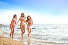 Schöne Mädchengruppe, die einen Bikini, gehend in dem Meer trägt stockfoto