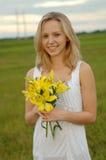 Schöne Mädchenholdingblumen Lizenzfreie Stockfotos