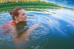 Schöne Mädchenschwimmen in einem Fluss Lizenzfreies Stockfoto