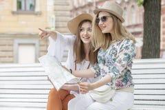 Schöne Mädchentouristen suchen nach einer Adresse auf der Karte, die auf der Bank sitzt Stockfotografie