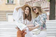 Schöne Mädchentouristen suchen nach einer Adresse auf der Karte, die auf der Bank sitzt Lizenzfreie Stockfotografie