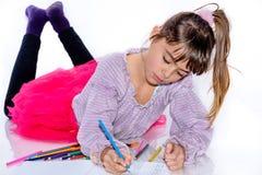 Schöne Mädchenzeichnung mit acht Jährigen mit Farbe zeichnet an Stockbild