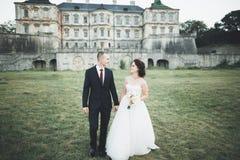 Schöne Märchenjungvermähltenpaare, die nahe altem mittelalterlichem Schloss umarmen lizenzfreie stockbilder