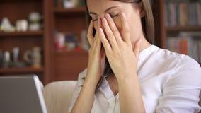 Schöne müde betonte überarbeitete Geschäftsfrau, die zu Hause an Wohnzimmer des Laptops arbeitet Rubing ihre Augen stock footage