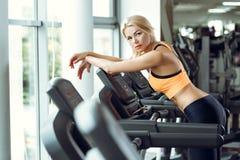 Schöne müde blonde Frau auf Tretmühle in der Turnhalle nach Training Stockbild