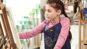 Schöne Malerei des kleinen Mädchens auf dem Gestell unter Verwendung der Ölfarben am Kunststudio stock video