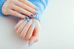 Schöne Maniküre des neuen Jahres Blaue Nägel mit schwarzem Entwurf und Bergkristallen platz stockfotografie