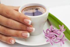 Schöne manikürte Hand mit französischen Nägeln und Tasse Kaffee und Blumen an der Untertasse Lizenzfreie Stockfotos