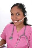 Schöne medizinische Empfangsdamen-tragender Kopfhörer Lizenzfreies Stockfoto