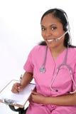 Schöne medizinische Empfangsdamen-tragender Kopfhörer Lizenzfreie Stockfotografie