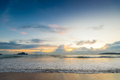 Schöne Meereswellen gießen in den Sonnenuntergang des sandigen Strandes Lizenzfreies Stockfoto