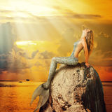Schöne Meerjungfrau, die auf einem Felsen sitzt Stockfoto