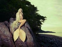 Schöne Meerjungfrau, die auf Felsen sitzt Stockfoto