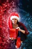 Schöne Mittelalterfrau in rotem Parteisankt-Hut, der mit Geschenken sitzt Stockfotografie