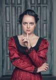 Schöne mittelalterliche Frau im roten Kleid, das Ruhegeste macht stockbild