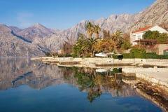 Schöne Mittelmeerlandschaft mit den Bergen und Stadt, reflektiert im Wasser Montenegro, Bucht von Kotor, Dobrota-Stadt Stockfotos