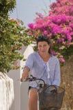 Schöne mittlere Frau auf ein Retro- Fahrrad in Andros-Insel lizenzfreie stockfotografie