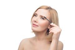 Schöne mittlere Greisin, die Augenbrauengel anwendet Lizenzfreie Stockfotografie