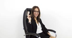 Schöne mittlere Greisin sitzt in einem schwarzen ledernen Bürostuhl und hält goldene Kreditkarte in der Hand stock video footage