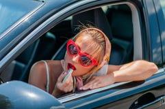 Schöne Modefrau, die auf Lippenstift in das Auto sich setzt stockfoto