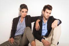 Schöne Modefrau, die nahe bei ihrem Freund sitzt Lizenzfreie Stockfotos