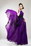Schöne Modefrau im violetten langen Kleid Stockfoto