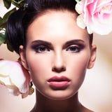 Schöne Modefrau mit rosa Blumen in den Haaren Stockfoto