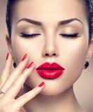 Schöne Modefrau mit rotem Lippenstift und roten Nägeln lizenzfreie stockfotografie
