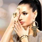 Schöne Modefrau mit schwarzem Make-up und goldener Maniküre lizenzfreie stockbilder