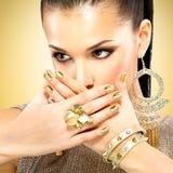 Schöne Modefrau mit schwarzem Make-up und goldener Maniküre lizenzfreie stockfotos