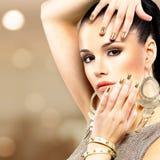 Schöne Modefrau mit schwarzem Make-up und goldener Maniküre Lizenzfreie Stockfotografie