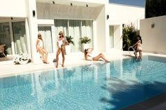 Schöne Modelle im Badeanzug, werfend nahe luxuriösem Schwimmen poo auf Stockfoto