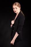 Schöne moderne blonde Dame im Anzug auf schwarzem Hintergrund Stockbilder