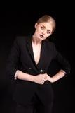 Schöne moderne blonde Dame im Anzug auf schwarzem Hintergrund Lizenzfreie Stockbilder