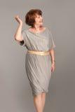 Schöne moderne fällige Frau im grauen Kleid Lizenzfreie Stockfotografie