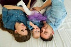 Schöne moderne Familie beim Jeanskleidlügen Stockfoto