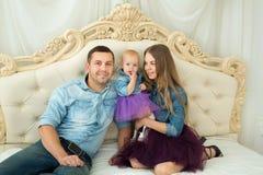 Schöne moderne Familie im Jeanskleidungssitzen Stockbild