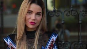 Schöne moderne Frau, die nahe Luxusgebäude aufwirft stock footage