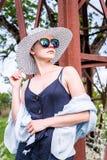 Schöne moderne Frau, die in die Straße, in die tragende Sonnenbrille, in das hübsche Kleid, in einen Hut und in Schal geht Arbeit lizenzfreie stockfotografie