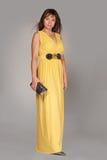 Schöne moderne Frau im langen gelben Kleid. Stockfotos