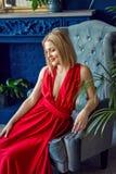 Schöne moderne Frau im roten Kleid sitzen auf dem Sessel an der Hintergrundblauwand Abschluss oben Stockfotografie